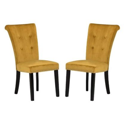 An Image of Wodan Velvet Dining Chair In Mustard With Black Legs In A Pair
